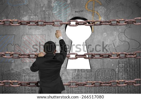 Businessman climbing on old iron chain for keyhole door with blank white view and business concept doodles wall background - stock photo