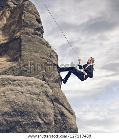 businessman climbing on the rocks - stock photo
