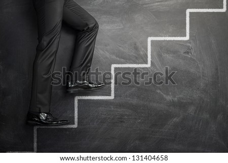Businessman climbing the career stairs drawn on a chalkboard with copy space - stock photo