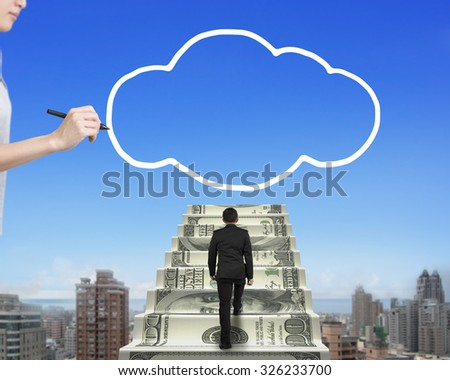 Businessman climbing the money stairs toward white cloud shape with female hand holding pen drawing, in blue sky cityscape background. - stock photo