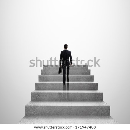 businessman climbing to stairs on gray background - stock photo