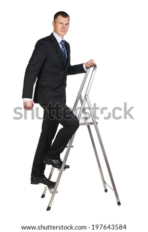 Businessman climbing up a stepladder with his gaze focused on camera . Isolated against a white background - stock photo
