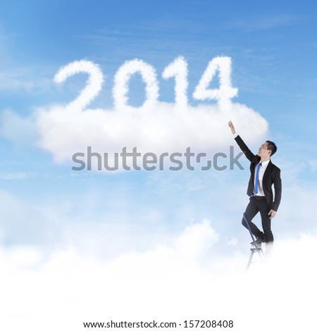 Businessman climbing upward on the stair of cloud to 2014 to gain his success - stock photo