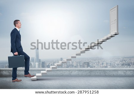 Businessman climbing with briefcase against cityscape - stock photo