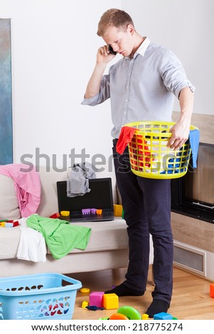 Businessman collecting dirty clothes at home, vertical