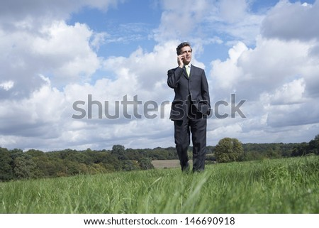 Businessman communicating on mobile phone in field against cloudy sky