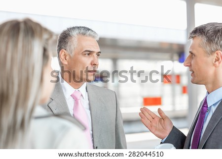 Businessman communicating with colleagues on railroad platform - stock photo
