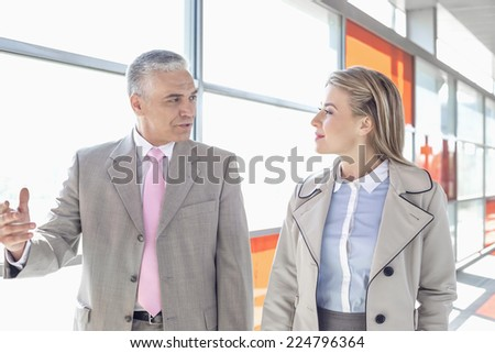 Businessman communicating with female colleague while walking in railroad station - stock photo
