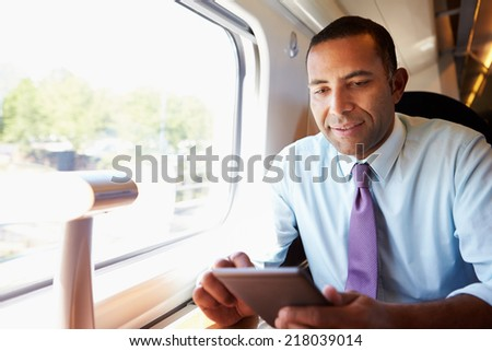 Businessman Commuting On Train Reading E Book - stock photo