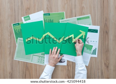 Businessman composing a successful financial chart with green arrow pointing up, he is using paper cuts, financial achievement and green business concept - stock photo