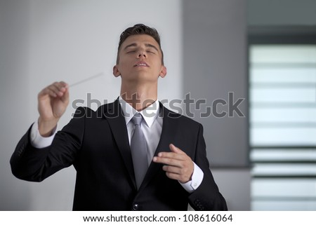 Businessman conducting his work and business with his baton - stock photo