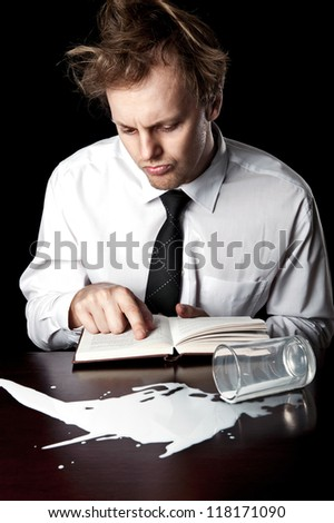 Businessman consulting manual book for help with his knocked over spilled glass of milk, abstract concept desaturated with black background - stock photo