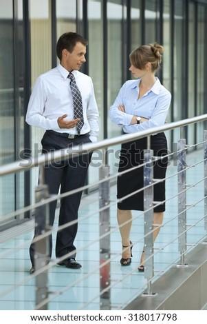 Businessman conversing with businesswoman at corridor - stock photo