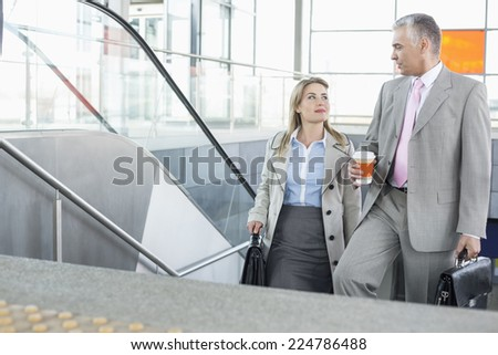 Businessman conversing with female colleague while walking up stairs in train station - stock photo