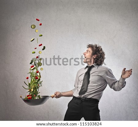 Businessman cooking vegetables with a pan - stock photo