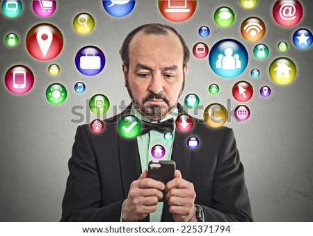 businessman corporate executive using texting on smartphone with social media mobile phone application symbols icons coming flying out of cellphone isolated grey wall background. 4g data plan concept  - stock photo