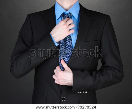 businessman correcting a tie on black background - stock photo