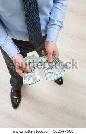 Businessman counting dollars, view from above - stock photo