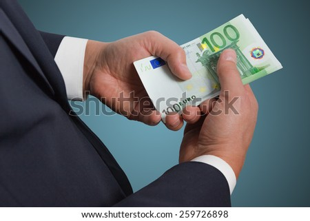 Businessman counts money on blue background. Hand holding money.