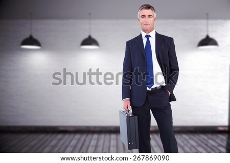 Businessman crossing finish line and cheering against grey room - stock photo