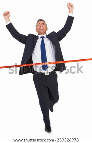 Businessman crossing finish line and cheering on white background - stock photo