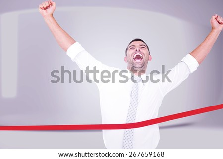 Businessman crossing the finish line against white abstract room - stock photo