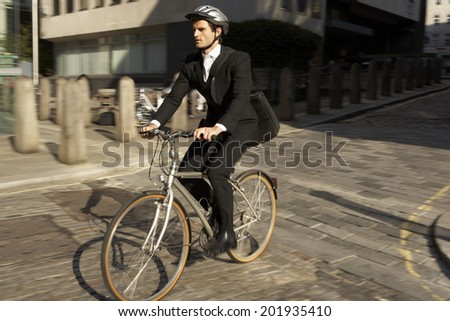 Businessman cycling to work - stock photo