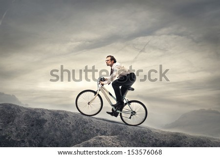 businessman cycling with fatigue in the high mountains - stock photo