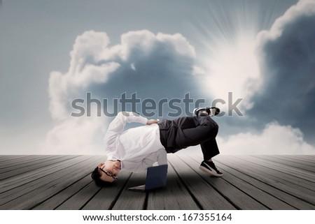 Businessman dancing while working on laptop symbolizing flexibility - stock photo