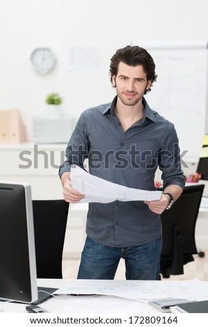 Businessman dealing with paperwork in the office standing behind his desk with an open spreadsheet in his hand smiling at the camera - stock photo