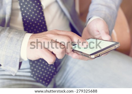 businessman dialing mobile phone with vintage color tone effect - stock photo