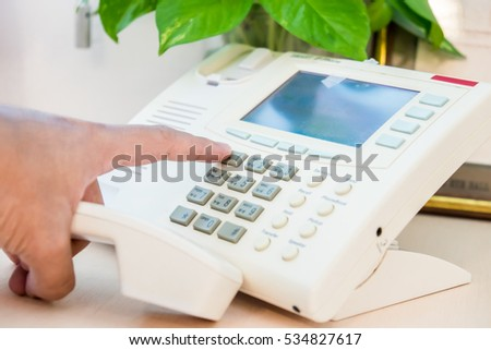 businessman dialing voip phone in the office, keyboard and monitor detail in the background with vintage color tone effect .Male hand holding phone receiver over telephone