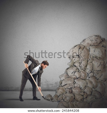 Businessman digs to remove an obstacle rock - stock photo
