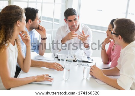 Businessman discussing with colleagues at conference table in office - stock photo