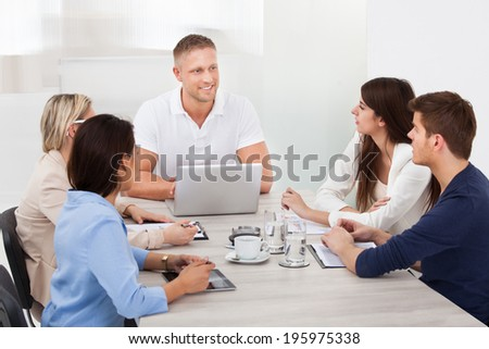 Businessman discussing with colleagues in meeting at desk - stock photo