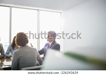 Businessman discussing with female team in conference room - stock photo