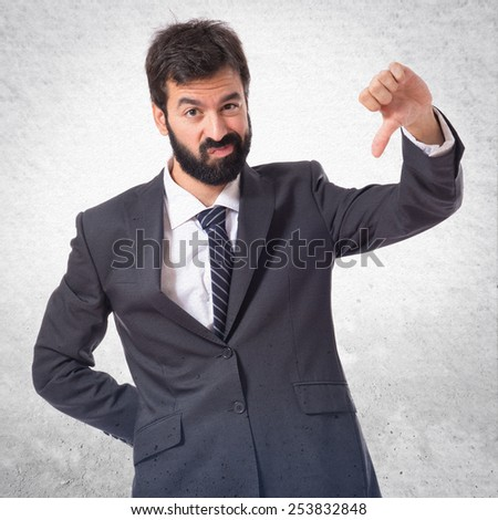 Businessman doing a bad signal over textured background - stock photo