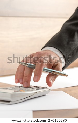 Businessman doing a calculation on a manual desk top calculator, close up of his hand holding a pen. - stock photo