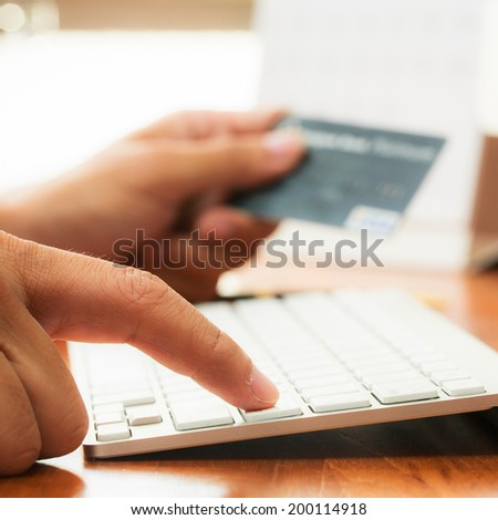 Businessman doing online banking, making a payment or purchasing goods on the internet entering his credit card details on a pc, close up view of his hands - stock photo
