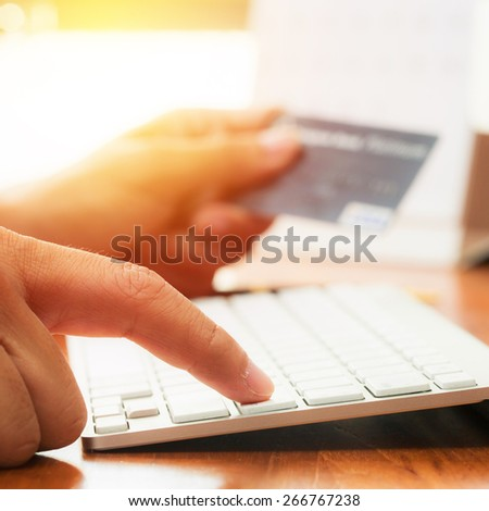 Businessman doing online banking, online shopping, making a payment or purchasing goods on the internet entering his credit card details on a pc, close up view of his hands. Vintage filter. - stock photo