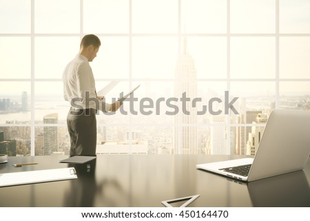 Businessman doing paperwork in office with laptop, clipboard and other items on desktop. Window with New York city view in the background. Toned image. 3D Rendering - stock photo