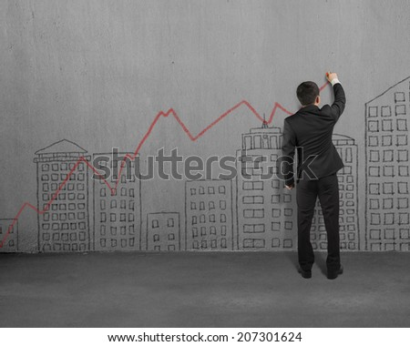 Businessman doodles on concrete wall - stock photo