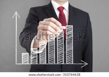 Businessman drawing a growing chart with chalk.  - stock photo