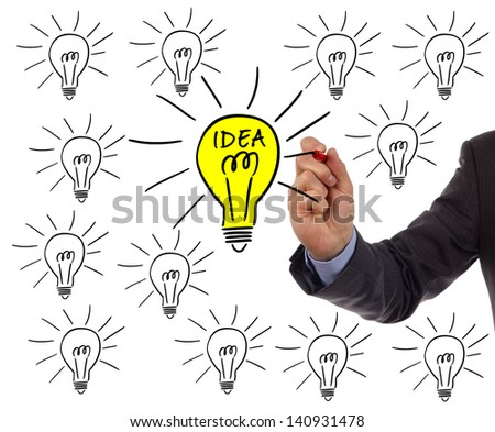 Businessman drawing a light bulb on a whiteboard concept for bright idea and inspiration - stock photo