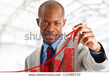 Businessman drawing a positive graph