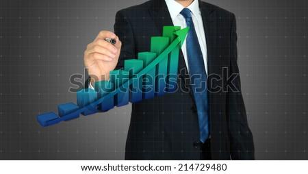 Businessman drawing a rising arrow over a bar graph  - stock photo