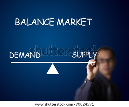 businessman drawing balance of demand and supply market on lever - stock photo