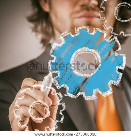 Businessman Drawing Blue and White Conceptual Gears in Close up, on Glass Board Using Marker. - stock photo