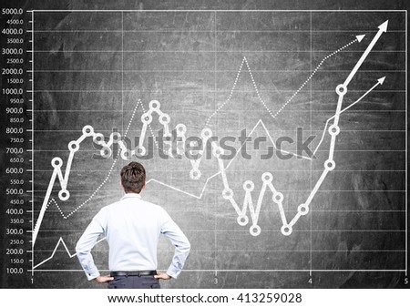 Businessman drawing business chart on dark grey surface - stock photo