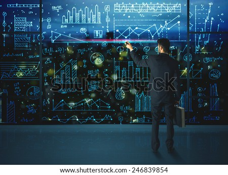 Businessman drawing business statistics on glass wall - stock photo